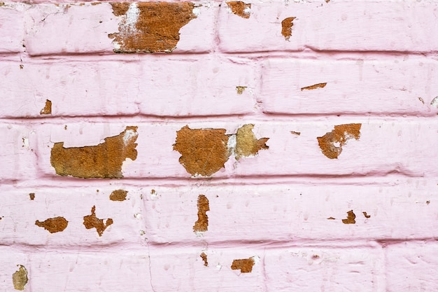 Red pink brick textured wall with damage background. old grunge industrial building. worn dampness painted brickwork