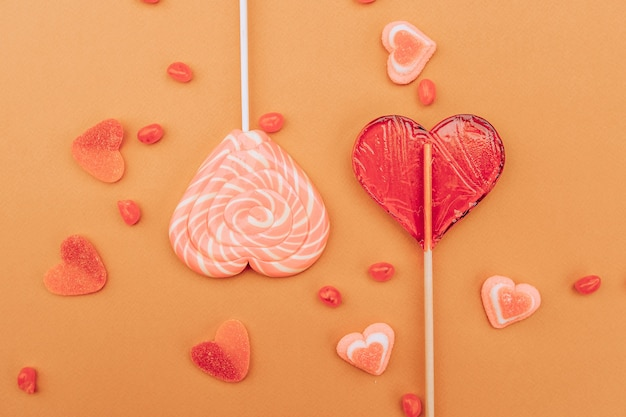 Red pink caramel and marmalade hearts on an orange background. st. valentine's day .