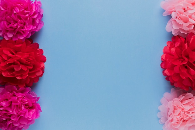 Red and pink decorative flower arrange in row over blue surface