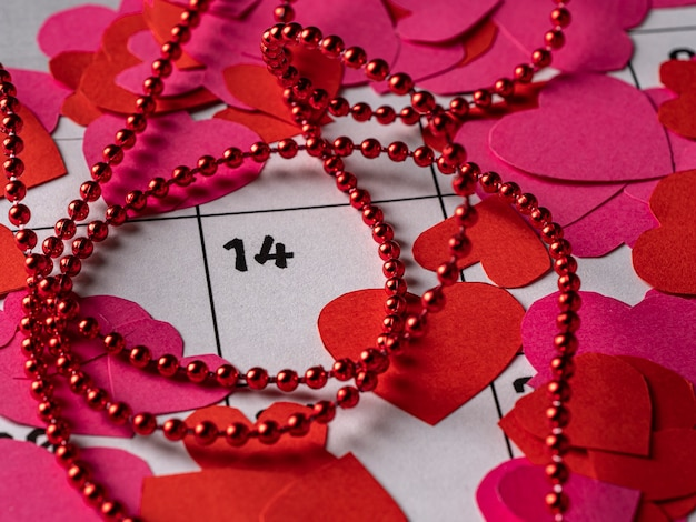 Red and pink hearts and ribbon on white calendar with valentine's day