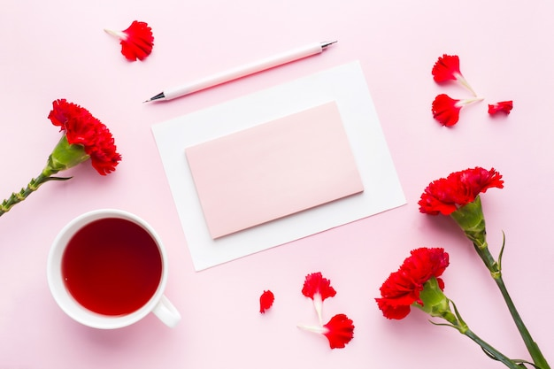 Red-pink objects. cup of tea, carnation flowers notepad for text on pastel pink background. copy space. top view flat lay