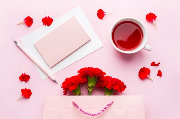 Red-pink objects. cup of tea, carnation flowers notepad for text on pastel pink background.