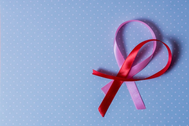 Red and pink ribbon breast cancer awarerness on blue background and copy space for text.