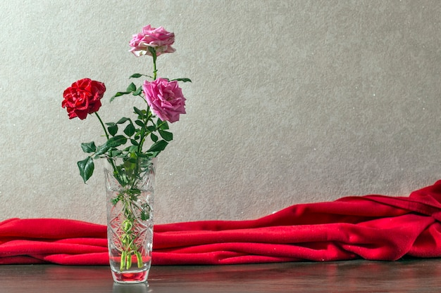 Red and pink roses in the crystal vase. interior fragment with red drapery.