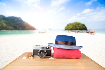 Red pink tower, blue hat, old vintage camera and shells over wooden floor on sunshine blue sky and ocean background