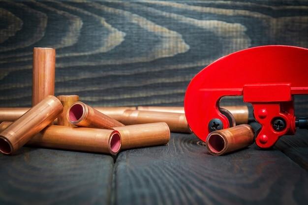 赤いパイプカッターと黒のビンテージボードの配管修理用コネクタ付き銅パイプ
