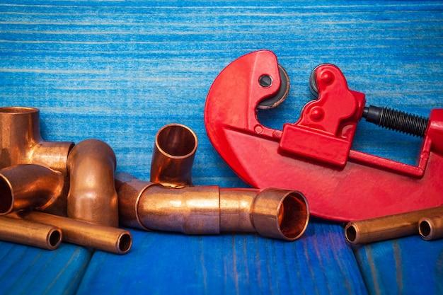 赤いパイプカッターと青いボード上のコネクタ付き銅パイプ