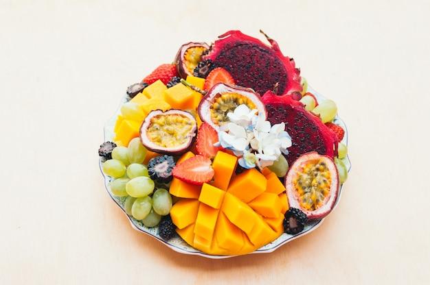 Red pitaya dragon fruit, grapes, mango and strawberry on plate
