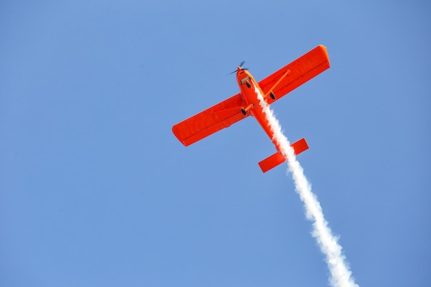 Red plane emits smoke in blue sky