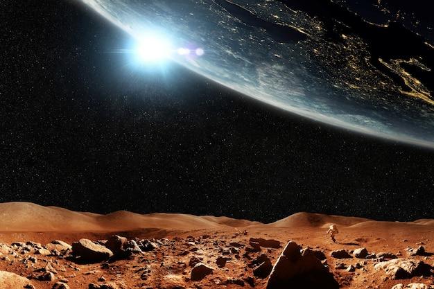 별과 행성 지구가 있는 붉은 행성 화성, 여행 공간 개념. 우주인 우주인은 우주가 내려다보이는 산이 있는 붉은 사막을 걸어갑니다.