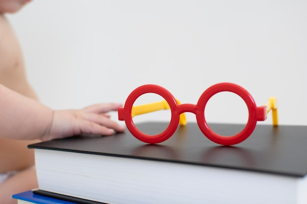 Red plastic baby eyeglasses on the book with blurred baby in the background