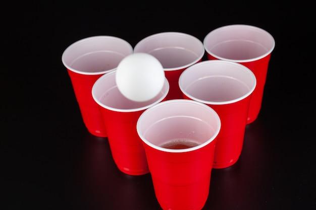 ビアポンのゲームのための赤いプラスチック製のカップとボール