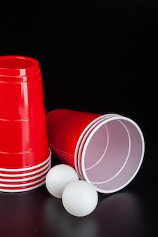 Red plastic cups and ball for game of beer pong