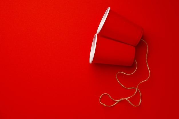 赤い上の糸で接続された赤いプラスチック製のコップ