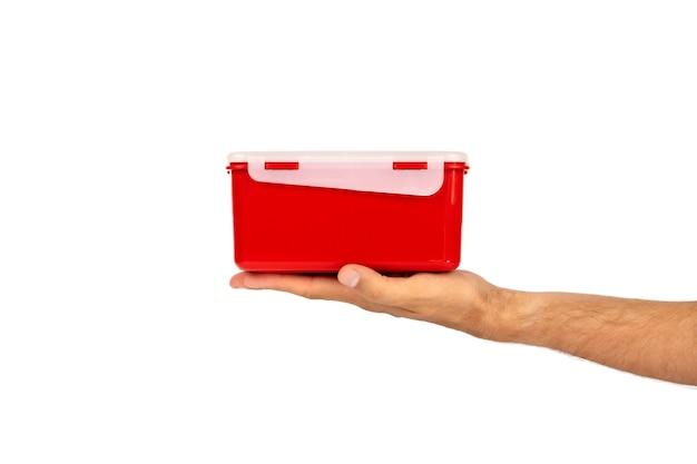 Красный пластиковый контейнер для пищевых продуктов в руке, изолированные на белом фоне. вид сбоку