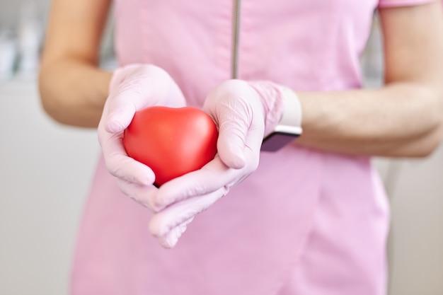 女性の手で赤いプラスチックの心