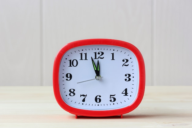 Red plastic rectangular alarm clock at twelve o'clock on a wooden table.