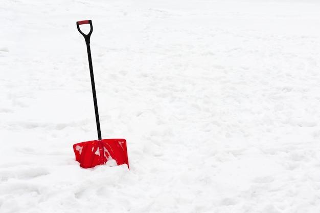 Красная пластиковая лопата с черной ручкой застряла в пушистом белом снегу.