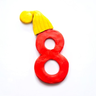 Red plasticine number 8 eight in a yellow winter cap on white background