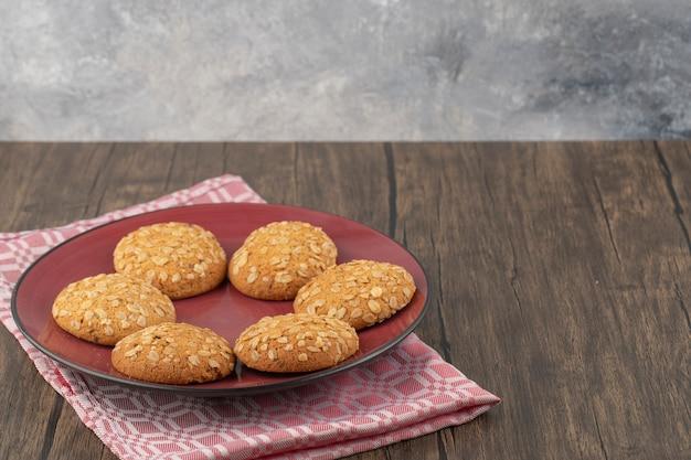 Piatto rosso pieno di biscotti di farina d'avena con semi e cereali posti sulla tavola di legno
