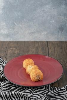 Красная тарелка вкусной выпечки кадаиф на деревянном столе.