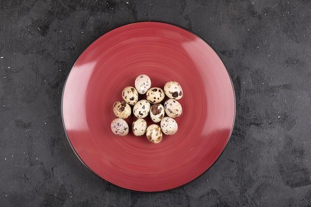 검은 색 표면에 원시 신선한 메 추 라 기 계란의 빨간 접시.