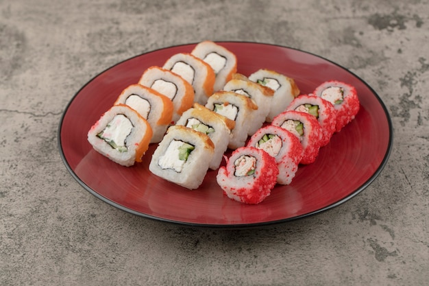 Red plate of various delicious sushi rolls on marble background