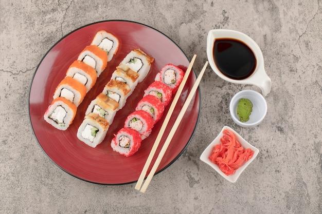 Piatto rosso di vari involtini di sushi con wasabi e zenzero sott'aceto sul tavolo di marmo