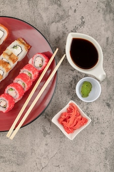Red plate of various sushi rolls with wasabi and pickled ginger on marble table