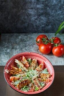 Un piatto rosso con insalata caesar e pomodori in superficie di marmo