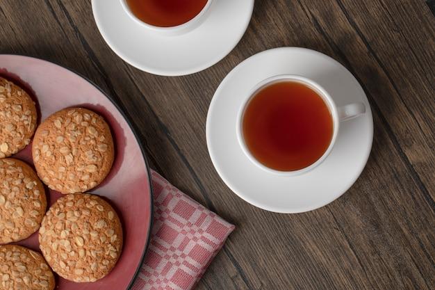 木製のテーブルにオートミールクッキーとお茶の赤いプレート