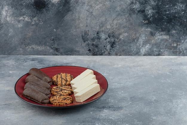 Un piatto rosso con biscotti di farina d'avena e bastoncini di cioccolato su uno sfondo di pietra.