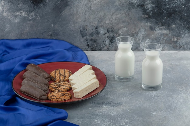A red plate with oatmeal cookies and chocolate sticks with glass of milk.