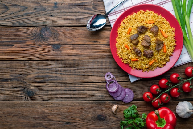 Red plate with pilaf on a white wooden table background with copysapce. top view