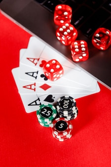 Red playing chips, dice and cards with aces closeup.