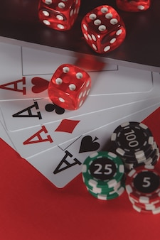 Red playing dice, chips and cards with aces on a red background. poker online concept. vertical image.