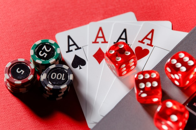 Red playing dice, gambling chips and cards with aces on a red background. online casino theme.