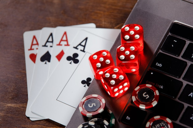 Red playing dice, gambling chips and cards on a wooden desk.