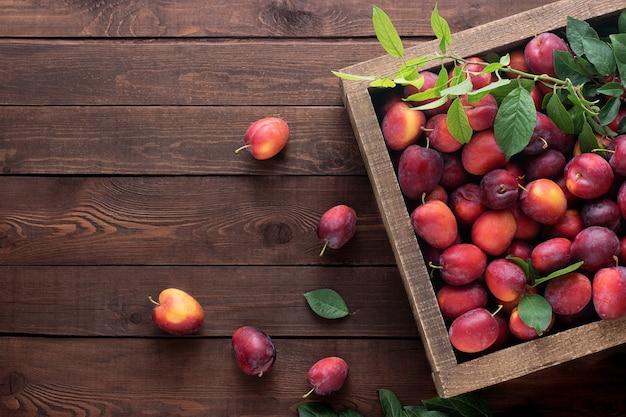 木製のテーブル、上面図、コピースペースの木製の箱に赤い梅。農場の収穫を収穫します。
