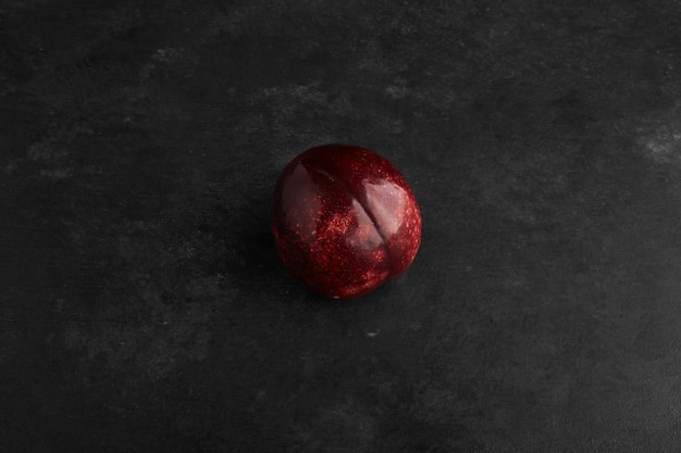 A red plum isolated on black background.