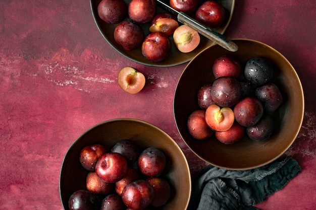Red plums in a bowl summer food flatlay