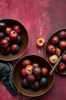 ボウルの夏の食べ物フラットレイの赤いプラム