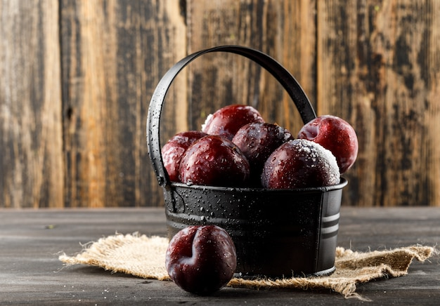 Red plums with piece of sack in a basket on wooden and grungy surface, side view.