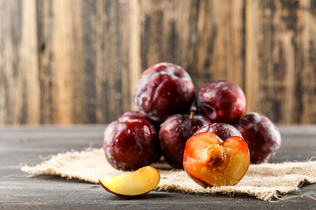 Red plums with piece of sack on wooden and grungy surface, side view.