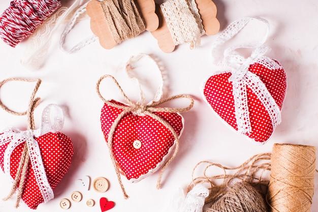 Красные сердечки из ткани в горошек украшают стол. процесс шитья и дизайна
