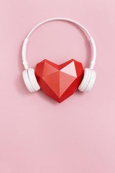 白いヘッドフォンで赤い多角形紙ハート。音楽のコンセプト。 djヘッドセット。最小限のスタイル。コピースペース付きのバナー。