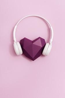 Красная многоугольная бумага в форме сердца фиолетового цвета в белых наушниках
