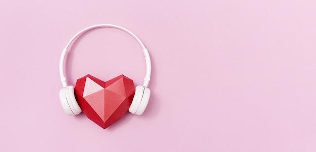 Red polygonal paper heart shape in white headphones. music concept. dj headset.