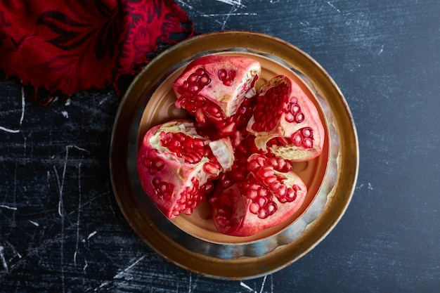 Red pomegranate cut into four pieces.
