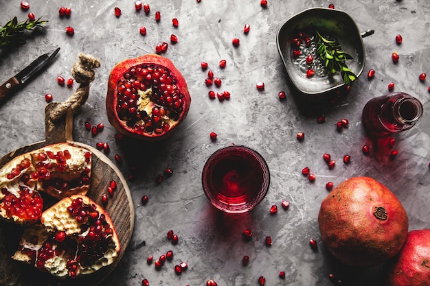 Red pomegranate juice in a glass, ripe and cut pomegranate and a sprig of mint on a gray concrete background. vitamin, antioxidant and health food concept. flat lay.top view.